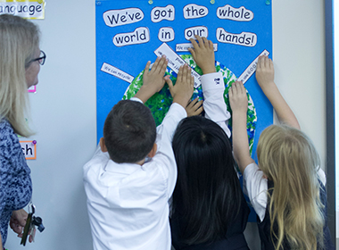 Junior School students reaching up on a poster of the globe