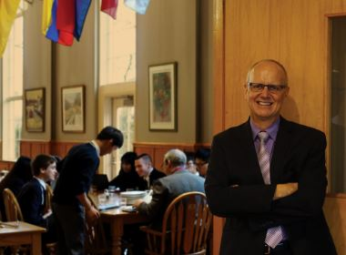 Peter Sturrup, Head of School, smiling in front of the Dining Hall